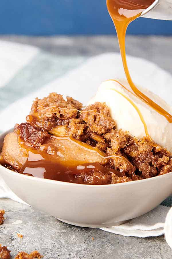caramel being drizzled over bowl of apple crumble with scoop of ice cream