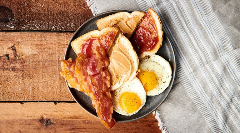 bacon on plate with eggs and toast above