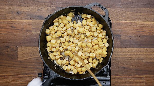 onion and potatoes being cooked in skillet