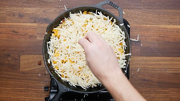 cheese being sprinkled over veggies