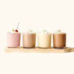 4 milkshakes lined up on cutting board