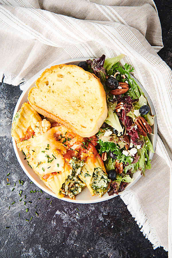 plate with manicotti, salad, and garlic bread above