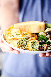 plate with manicotti, salad, and garlic bread held two hands