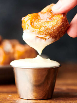 piece of monkey bread being dipped in frosting