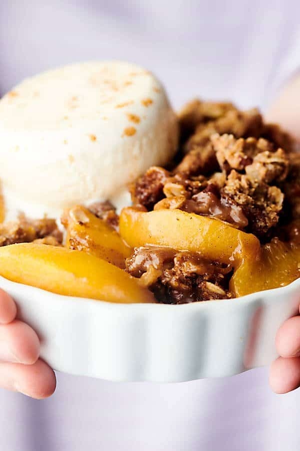 dish of peach crisp held two hands