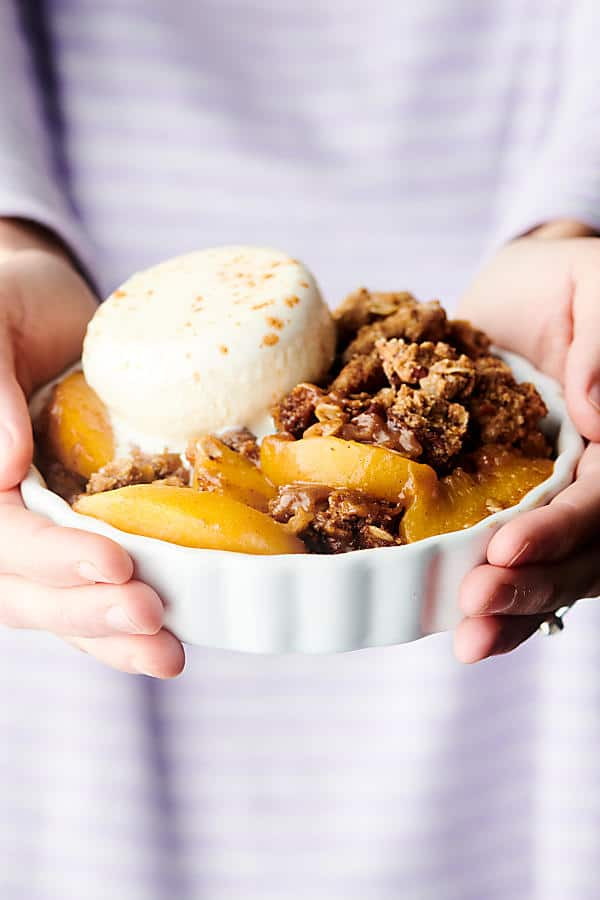 dish with peach crisp and scoop of ice cream held two hands
