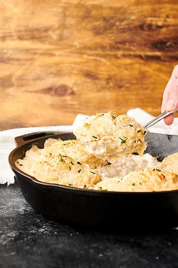 sausage gravy being scooped out of skillet with spoon