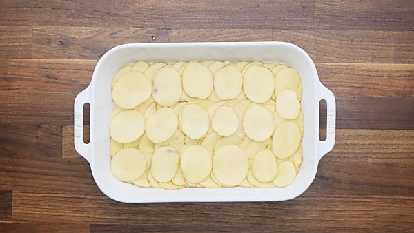 potato slices layered in baking dish
