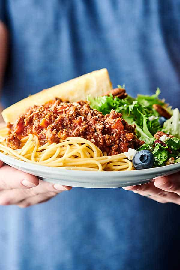 plate of spaghetti bolognese held two hands