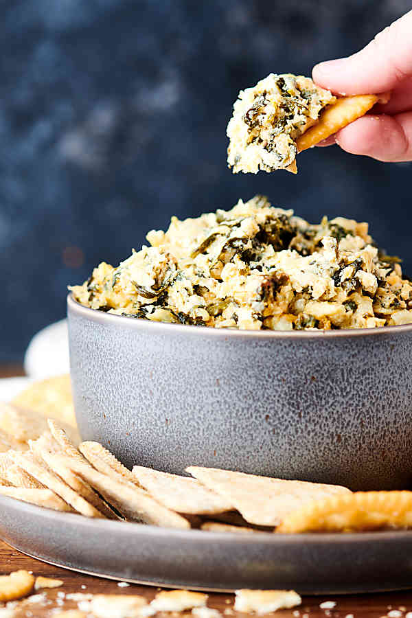 cracker being dipped into bowl of spinach artichoke dip