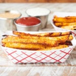 two dishes of air fryer french fries with condiments