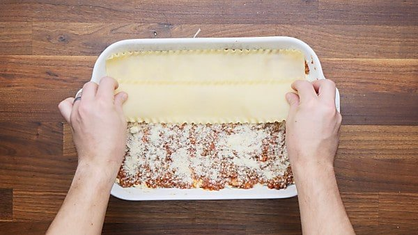 noodles being layered in baking dish