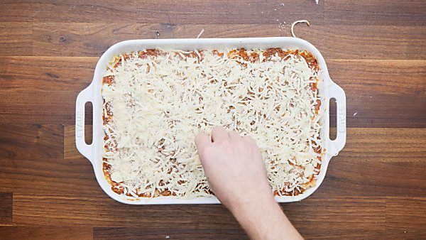 mozzarella being sprinkled on top of lasagna
