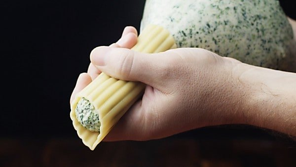 cheese mixture being piped into pasta tube