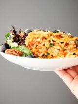 slice of vegetarian lasagna with salad on plate held