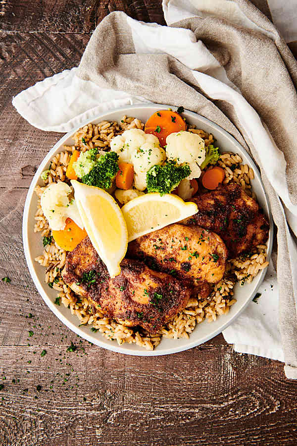 plate of chicken thighs with rice and veggies above
