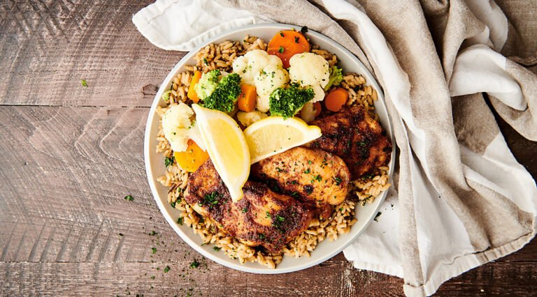 air fryer chicken thighs on plate with veggies and rice above