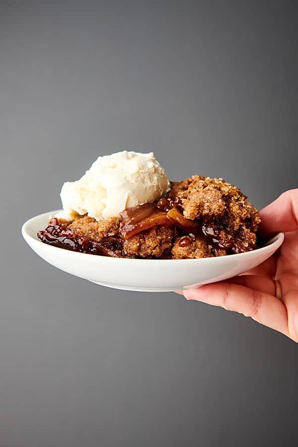 plate of apple cobbler with scoop of vanilla ice cream held