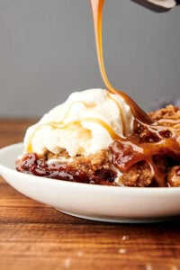 plate of apple cobbler being drizzled with caramel