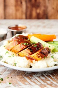 sliced buffalo chicken over mashed potatoes on plate with celery and carrots