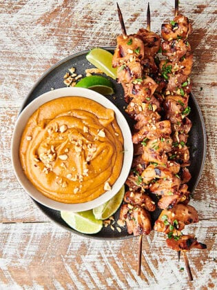 chicken satay skewers on plate with bowl of thai peanut sauce above