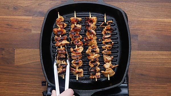 chicken skewers being grilled
