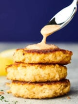 three crab cakes stacked being drizzled with sauce