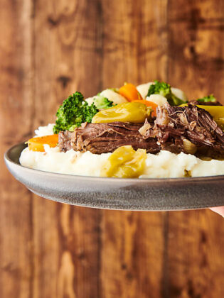 plate with mississippi roast over mashed potatoes with veggies held