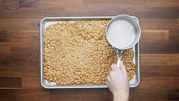 brittle being pressed onto baking sheet