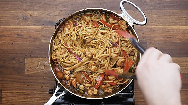 shrimp lo mein in saute pan being served with tongs