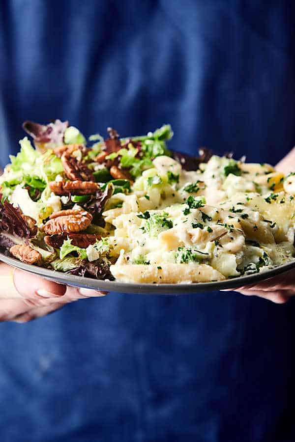 baked chicken alfredo on plate with salad held