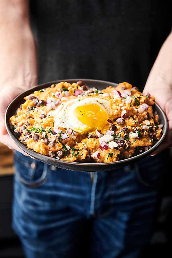 chilaquiles on plate with fried egg held