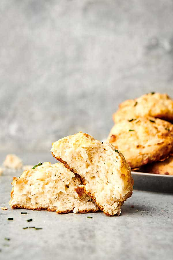two drop biscuits on counter, plate of biscuits behind