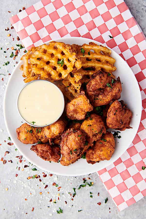 popcorn chicken on plate with waffle fries and ranch above