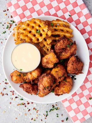 popcorn chicken with waffle fries and ranch on plate above