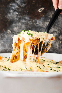 rigatoni being scooped out of baking dish with ladle