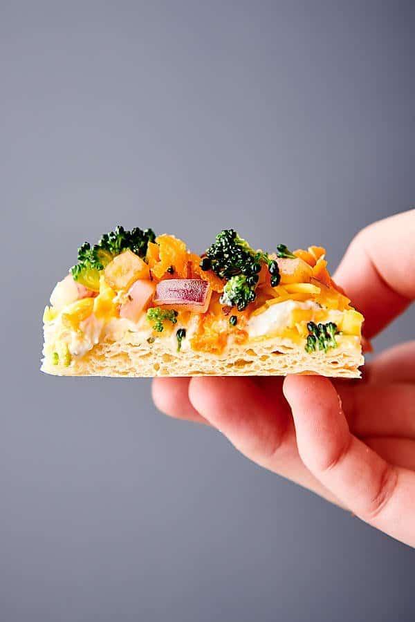 piece of veggie pizza held