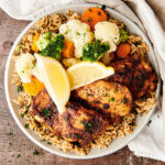 air fryer chicken thighs on plate with veggies above
