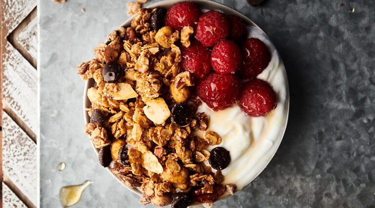 almond butter granola in bowl with yogurt and raspberries above