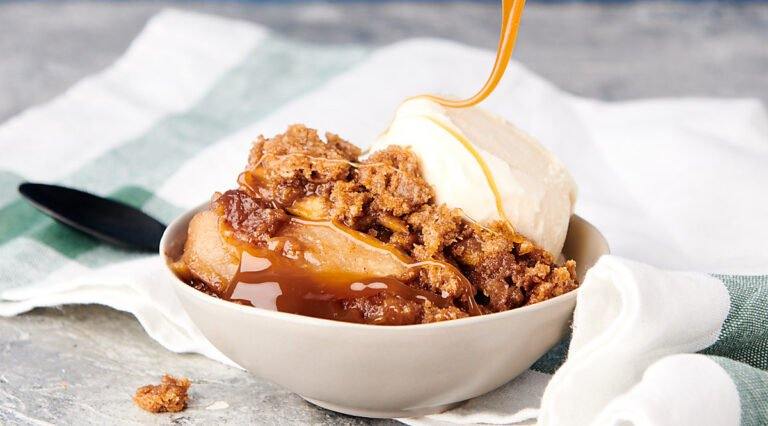 bowl of apple crumble being drizzled with caramel