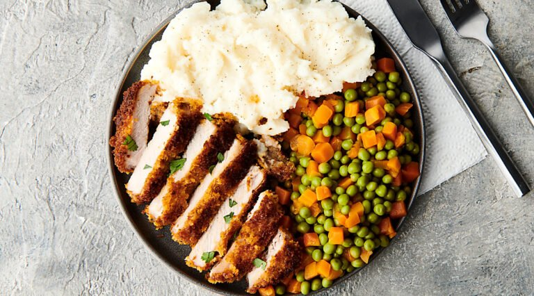 baked pork chop on plate with mashed potatoes and veggies above