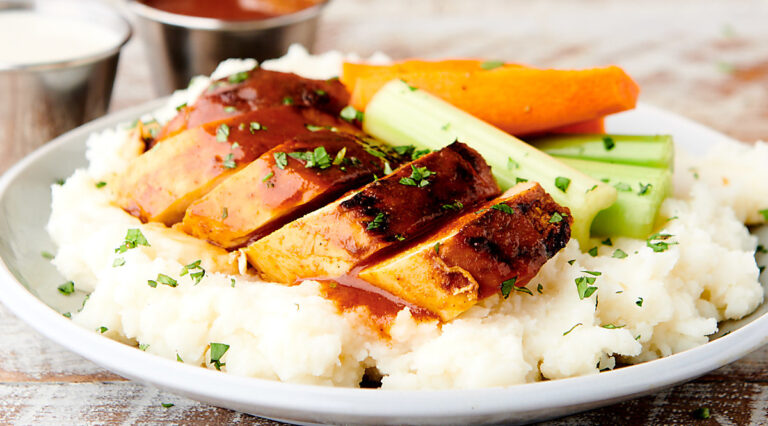 sliced buffalo chicken over mashed potatoes