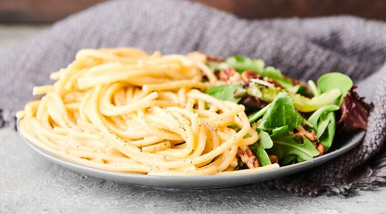plate of cacio e pepe with salad