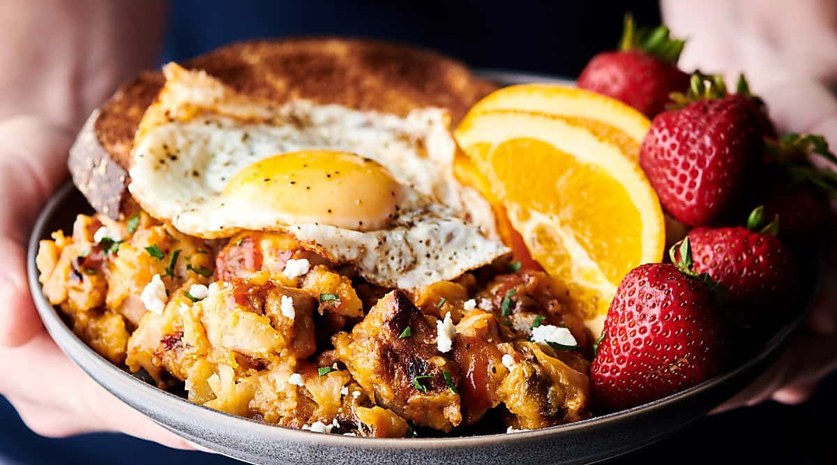 cheesy pork and potato breakfast skillet on plate held