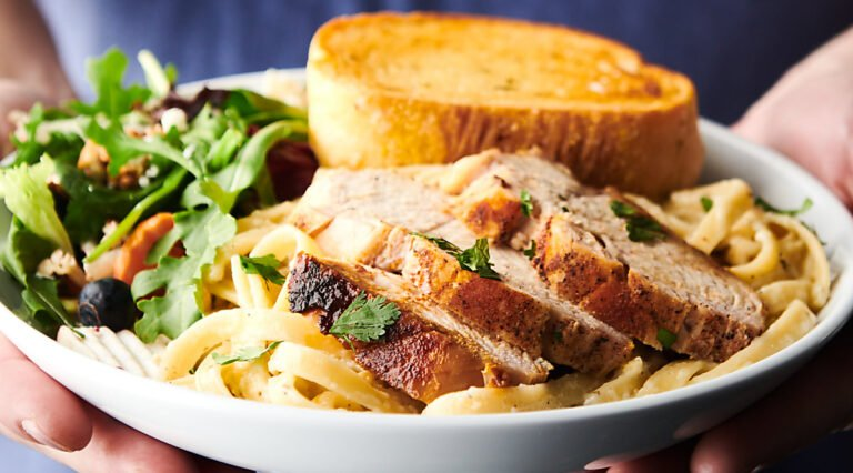 chicken alfredo on plate with salad and garlic bread