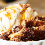 bowl with crockpot pumpkin dump cake and ice cream