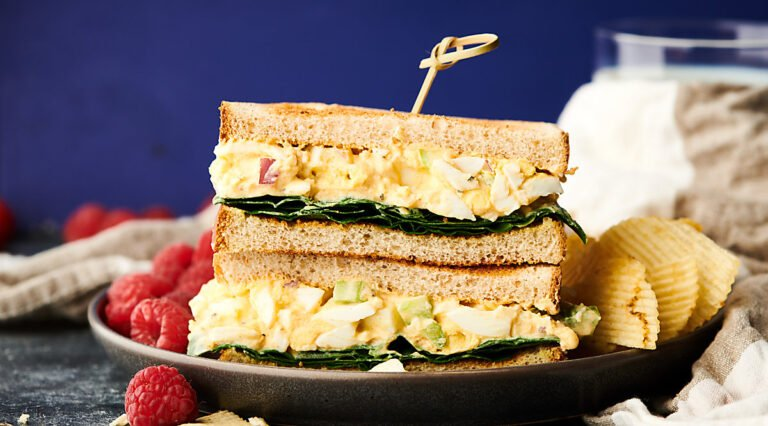 two halves of egg salad sandwich stacked on plate