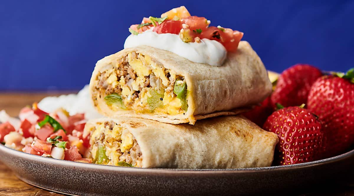 two halves of make ahead breakfast burritos stacked on plate with strawberries