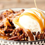 bowl of slow cooker carrot cake with ice cream and caramel
