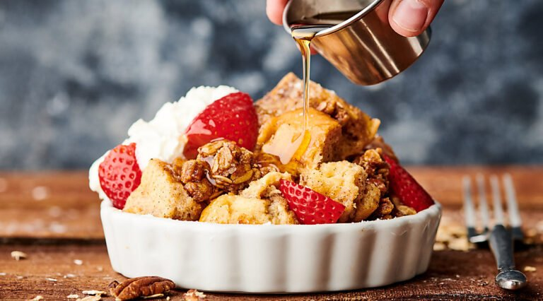 bowl of french toast casserole being drizzled with maple syrup